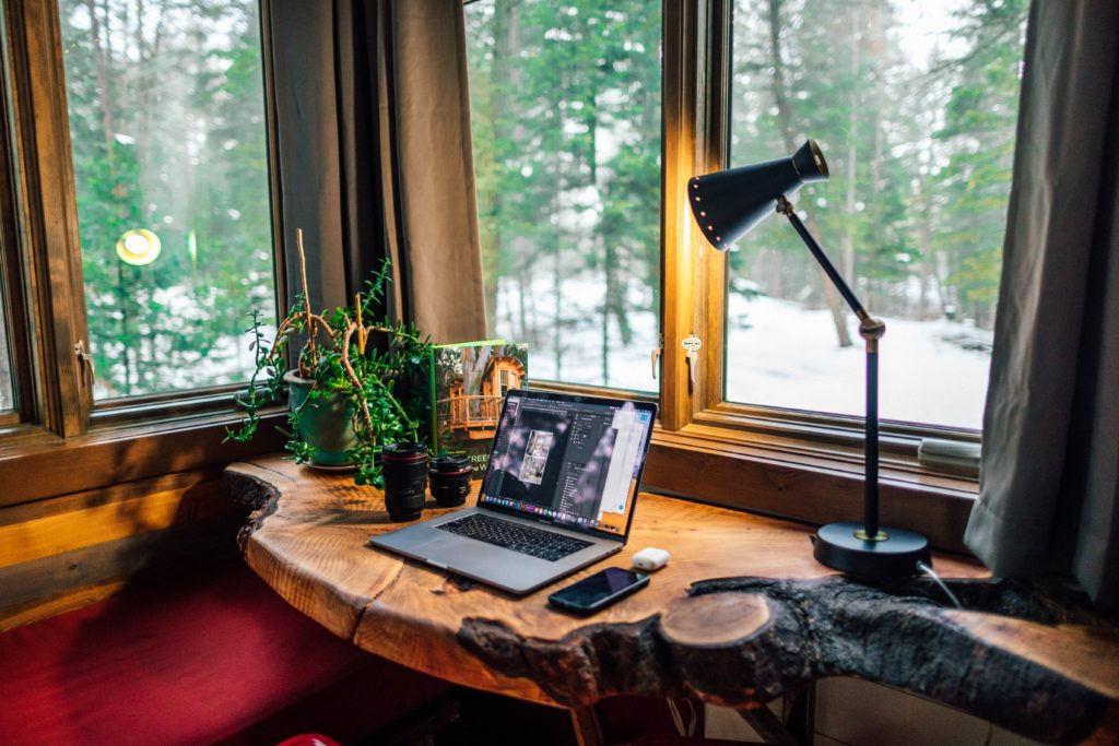 natural wood desk with laptop and lamp